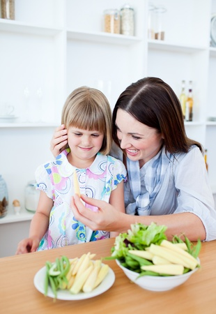 Smiling little girl eating vegetables with her mother photo