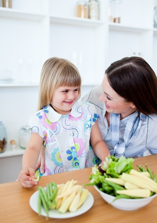 Attentive mother and her daughter eating vegetables photo