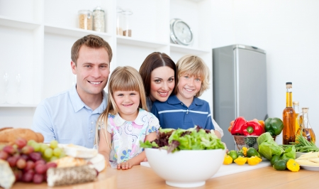 family meal: Smiling parents and their children preparing dinner together