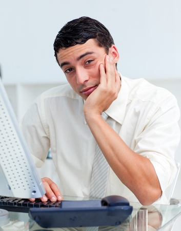 Bored Hispanic businessman at his desk Stock Photo - 10257011
