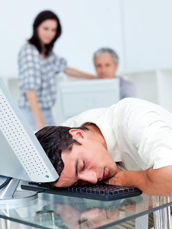 Tired businessman sleeping on his keyboard  photo