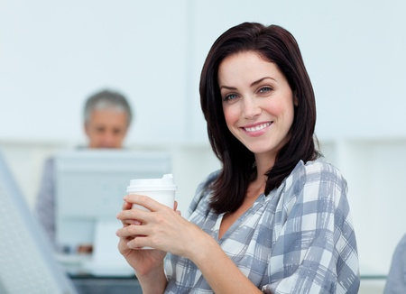 Glowing businesswoman drinking a coffee  photo