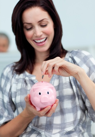Cheerful businesswoman saving money in a piggy-bank  photo