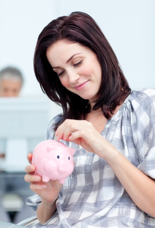 Glowing businesswoman saving money in a piggy-bank photo
