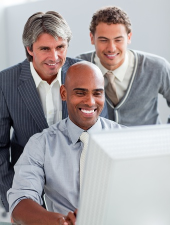 Positive businessmen helping their colleague at a computer Stock Photo - 10258315
