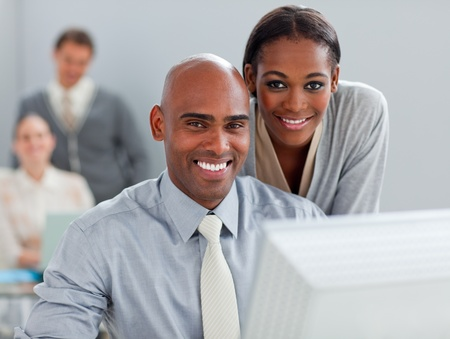 Charismatic businesswoman helping her colleague at a computer photo