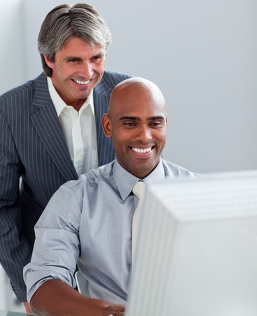 Positive business partners working at a computer together photo