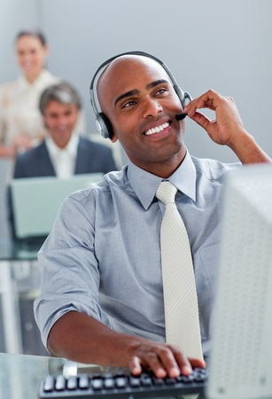 Cheerful businessman working at a computer with headset on photo