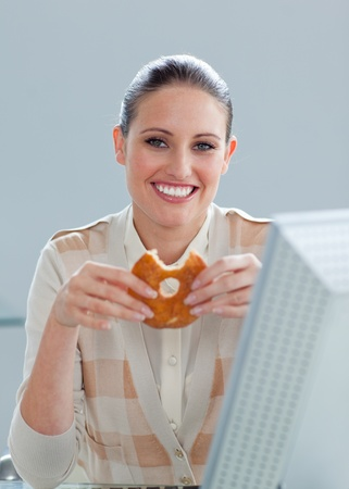 Smiling businesswoman eating a donut Stock Photo - 10256834