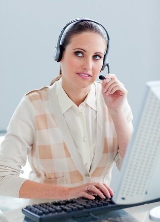 Pensive businesswoman working at a computer with headset on photo