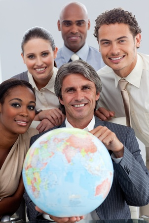 Cheerful Multi-ethnic business team showing a terrestrial globe photo