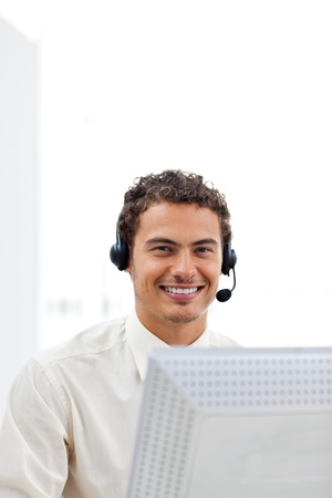 Smiling businessman working at a computer photo