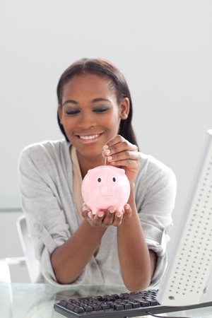 Afro-american businesswoman saving money in a piggybank Stock Photo - 10259334