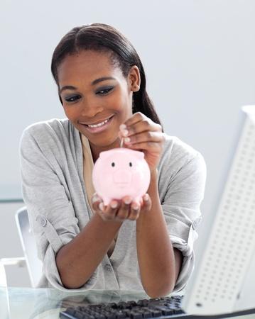 Assertive Afro-american businesswoman saving money in a piggybank  photo