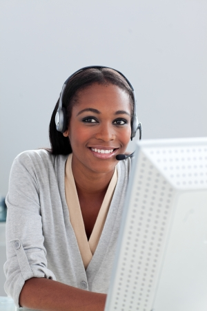 Delighted Afro-american businesswoman using headset  photo