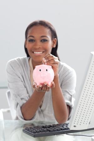 Smiling ethnic businesswoman saving money in a piggybank  photo
