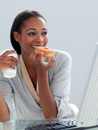 Ethnic businesswoman eating a donut at her desk  photo