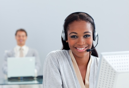 Smiling businesswoman using headset at her desk photo