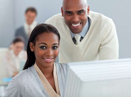 Ethnic businessman helping his colleague at a computer Stock Photo - 10256661