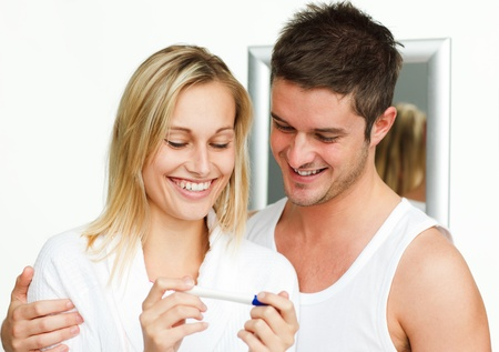Happy couple examining a pregnancy test photo
