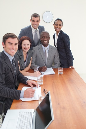 Five business people in a meeting smiling at the camera Stock Photo - 10240586