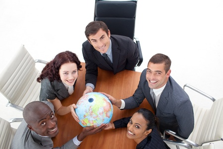 High view of happy business people holding a globe in a meeting  photo