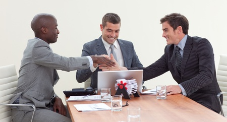 Happy businessmen in a meeting looking at a laptop Stock Photo - 10244889