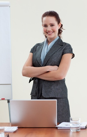 Beautiful businesswoman with folded arms in office photo