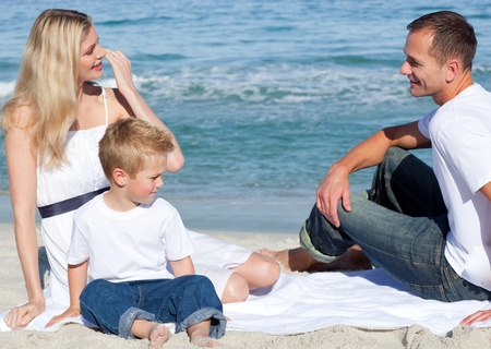 Smiling parents with their son sitting on the sand  photo