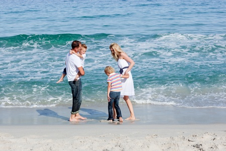 Happy family walking on the sand  photo
