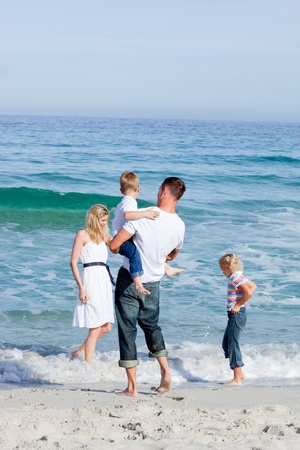 Affectionate family having fun at the beach photo