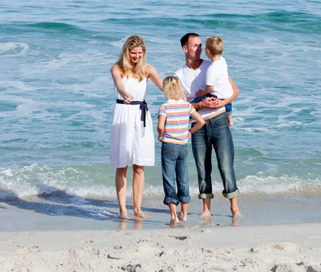 Happy family having fun on the sand  photo