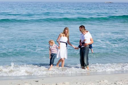 familia animada: Familia animada que se divierten en la playa Foto de archivo