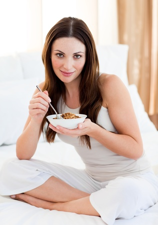 Brunette woman eating cereals sitting on bed photo