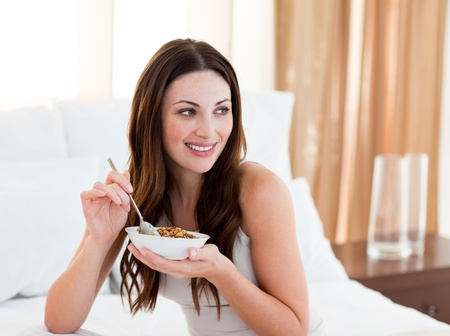 Pretty woman eating cereals sitting on bed photo