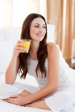 Beautiful woman drinking orange juice on bed photo