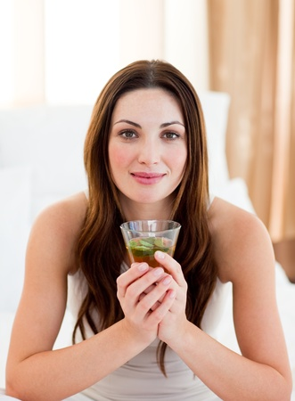 Young brunette woman drinking tea sitting on bed photo