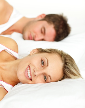 Portrait of a smiling couple sleeping on their bed  photo