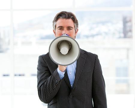 Mature businessman yelling through a megaphone photo