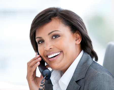 Portrait of a radiant business woman talking on phone photo