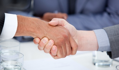 Close-up of confident business people closing a deal photo