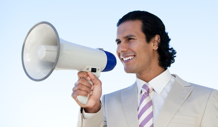 Portrait of a latin business man shouting through a megaphone photo
