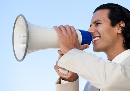 Portrait of an hispanic business man shouting through a megaphone photo