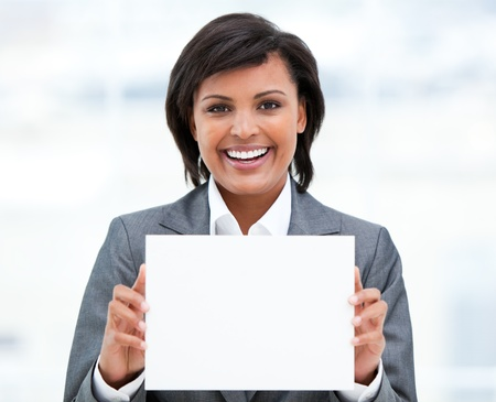 Smiling ethnic businesswoman holding a white card photo