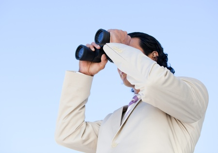 Portrait of an handsome business man looking through binoculars photo