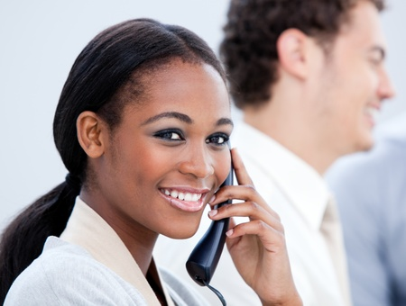 Smiling Afro-American businesswoman talking on phone photo