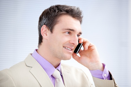 Positive businessman talking on phone photo