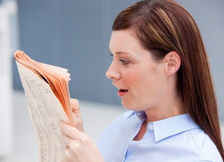 suddenness: Surprised businesswoman reading newspaper Stock Photo