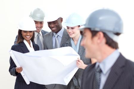 hard worker: Ingegnere guardando la sua squadra studiando un piano
