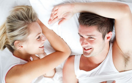Couple relaxing and smiling in bed photo